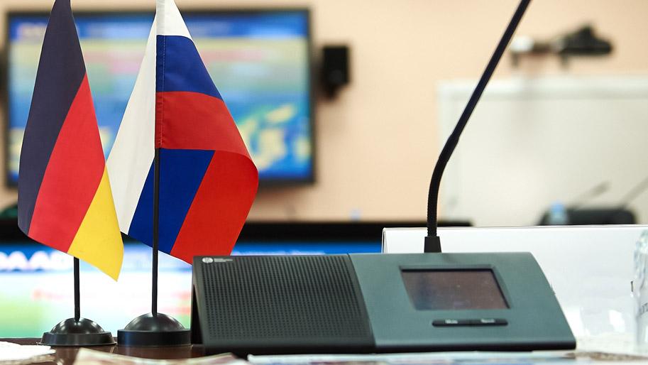 Russische und deutsche Flaggen stehen auf einem Konferenztisch.