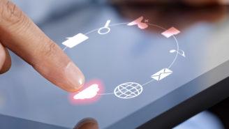Finger tippt auf einem Tablet-Computer auf ein Wolkensymbol.