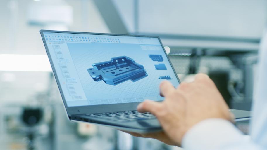 Hand hält Notebook mit technischer 3D-Skizze.