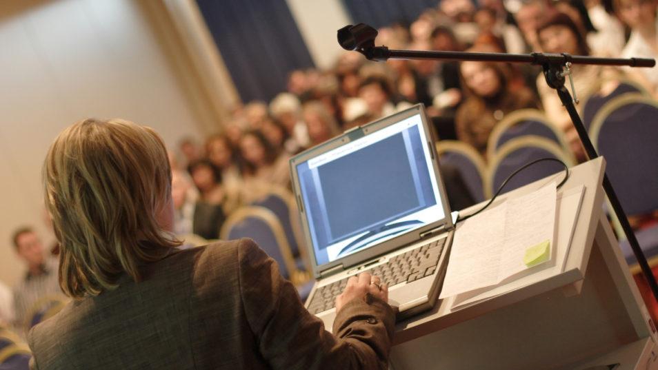 Eine Frau steht vor einem Publikum an einem Rednerpult mit Laptop.