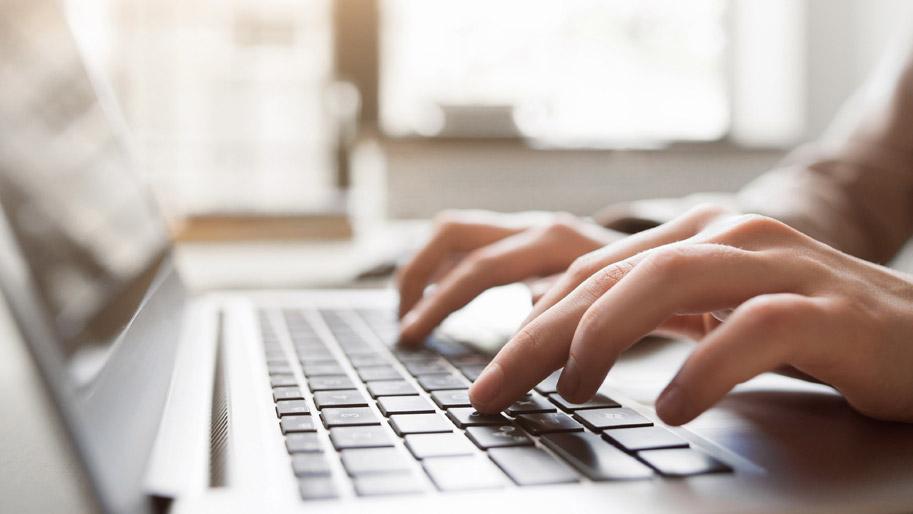 Hände tippen auf einer Laptop-Tastatur.
