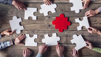 Hände schieben große Puzzleteile auf einem Tisch zusammen.