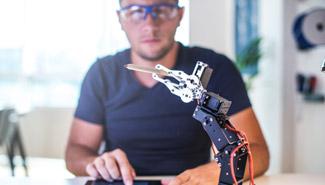 Ein Mann bedient per Tablet einen Roboter.