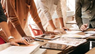 Vier Personen sind über einen Tisch mit Unterlagen gebeugt.