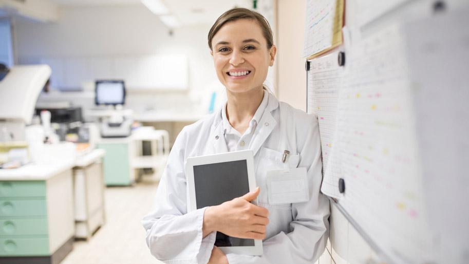 Eine Frau in weißem Kittel steht mit einem Tablet unterm Arm in einem Labor.