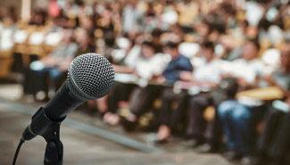 Nahaufnahme eines Mikrofons mit Publikum verschwommen im Hintergrund.