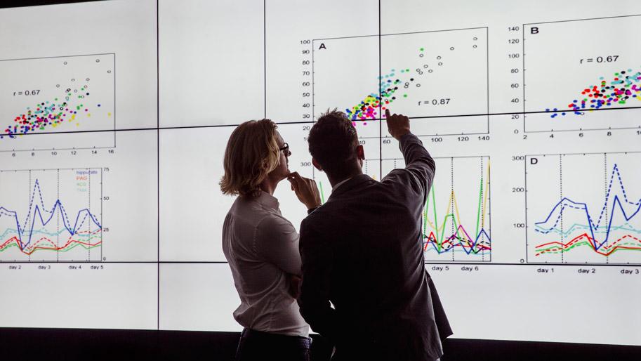 Zwei Männer analysieren Diagramme an einem großen Screen.