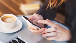 Hände einer Frau am Smartphone mit Kaffeetasse und Laptop auf dem Tisch.