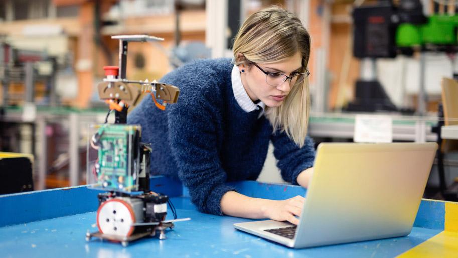 Eine junge Frau forscht an einer Apparatur.