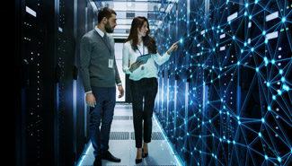 Ein Mann und eine Frau stehen in einem Serverraum an einer interaktiven Videowand.